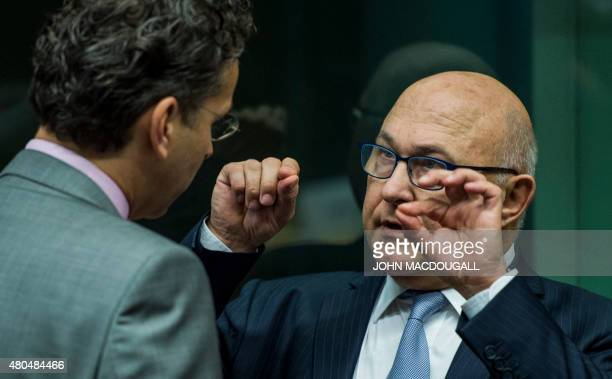 French Finance Minister Michel Sapin speaks with President of the Eurogroup Jeroen Dijsselbloem during a meeting of the Eurogroup finance ministers...