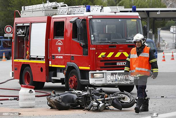 A French firefighter walks past a damaged motorcycle at the site of an accident involving a German tourist bus the motorcycle and three vehicles near...
