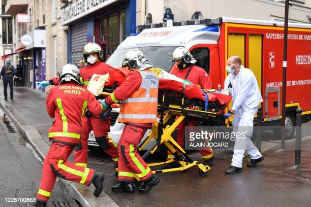 French firefighters carrying an injured person near the former offices of the French satirical magazine Charlie Hebdo following an alleged attack by...
