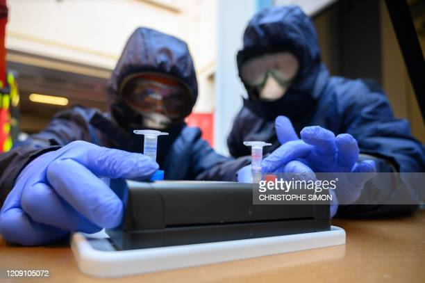 French firefighters from Marins Pompiers unit of Marseille wearing protective equipments as they working at the PCR machine on a mobile unit, which...