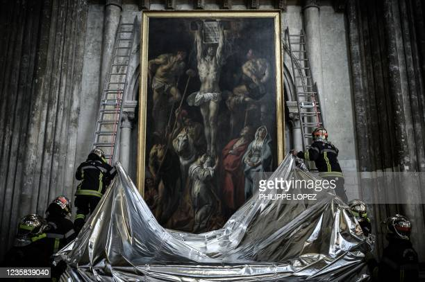 French firefighters protect a painting with a fireproof blanket during a fire drill aimed at preserving artworks displayed in the Saint-Andre...