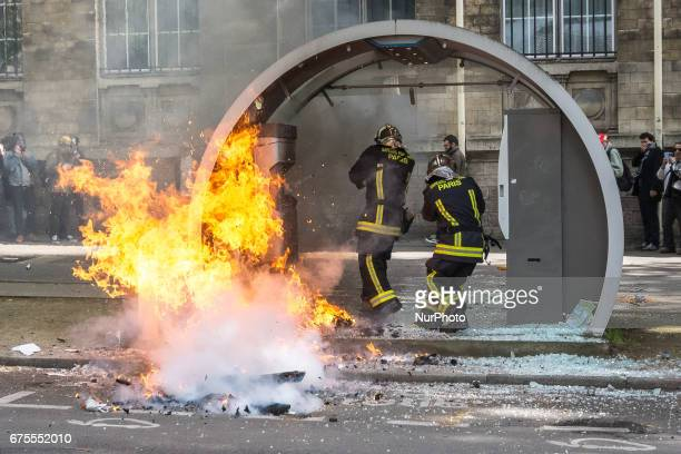 French firefighters protect their face as they approach a fire at an autolib station following clashes between demonstrators and French antiriot...