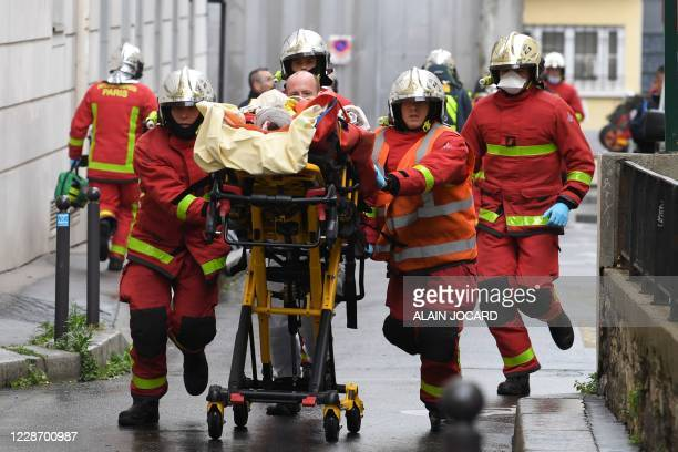 French firefighters push a gurney carrying an injured person near the former offices of the French satirical magazine Charlie Hebdo following an...