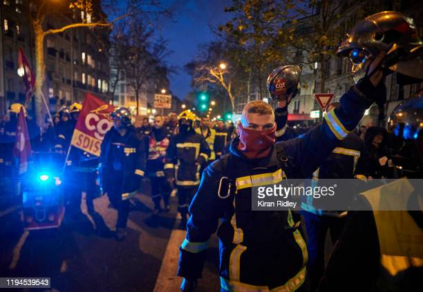 French fireman and members of the CGT union march through the streets of Paris chanting against President Macron as thousands take to the streets in...