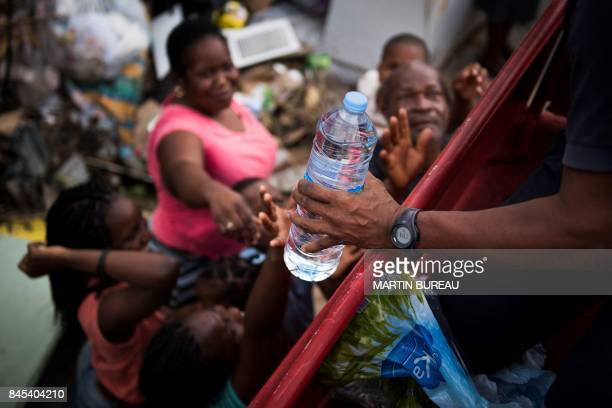 French firemen provide bottles of water to inhabitants of the Sandy Ground area of Marigot on September 10 2017 on SaintMartin island devastated by...