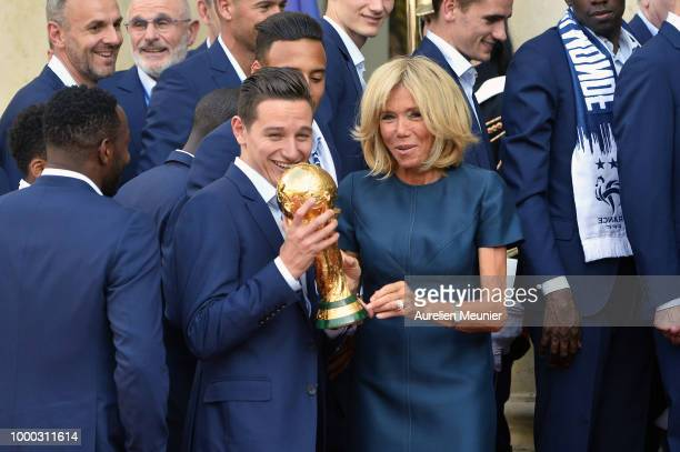 French First Lady Brigitte Macron holds up the World Cup trophy with Florian Thauvin as French President Emmanuel Macron receives the France football...