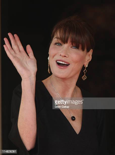 French First Lady Carla BruniSarkozy waves to photographers before entering Le Ciro's Resaturant to have lunch with the spouses of heads of state on...