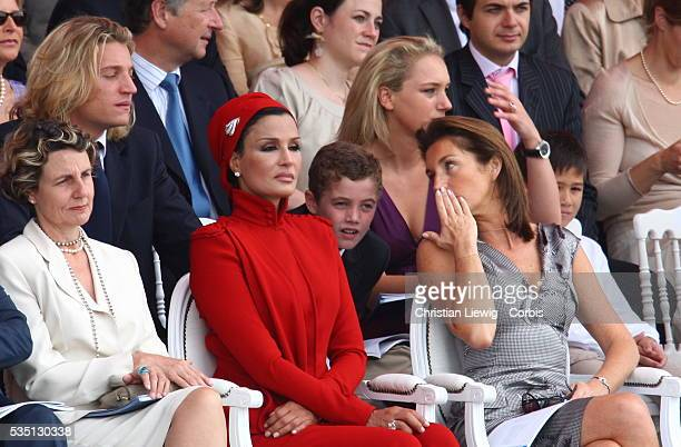 French first lady Cecilia Sarkozy speaks with her son Louis and the wife of the Emir of Qatar at the Bastille Day parade on the Champs Elysees