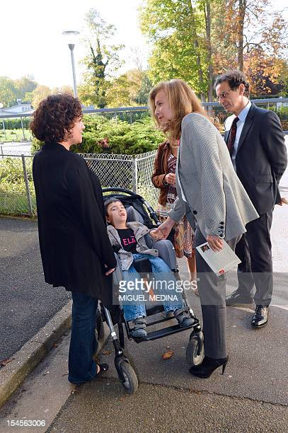 French first lady Valerie Trierweiler chats with a ill child and his mother at the Pierre et Marie Curie high school in L'IsleAdam outside Paris on...