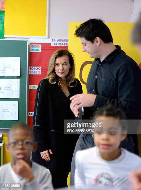 French First Lady Valerie Trierweiler talks to teacher Thomas Mourot during a class for disabled children using tablet computers on December 2 2013...