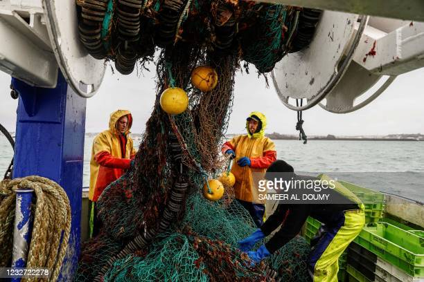 French fishermen gather in a net on their vessel near the port of Saint Helier off the British island of Jersey on May 6, 2021. - Around 50 French...
