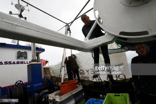 French fishermen hang a banner as fishing boats protest in front of the port of Saint Helier off the British island of Jersey to draw attention to...