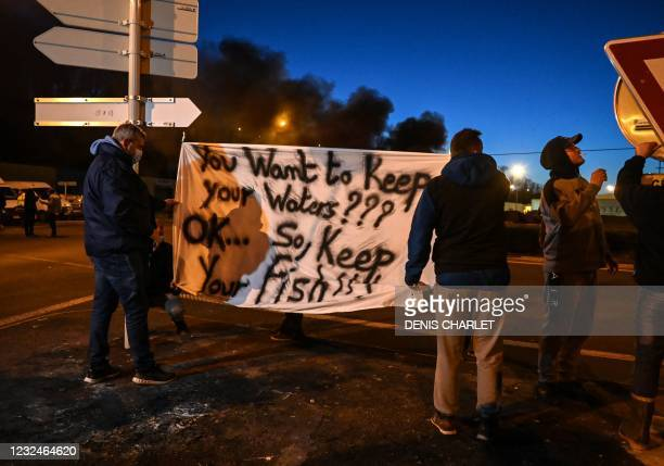 French fishermen stand near a banner as they gather as part of a protest action against the delay in granting licenses to access British waters at...