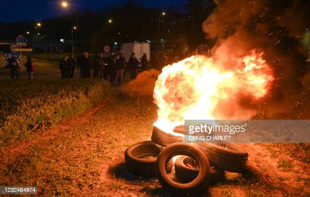 French fishermen stand near burning tyres as they gather as part of a protest action against the delay in granting licenses to access British waters...