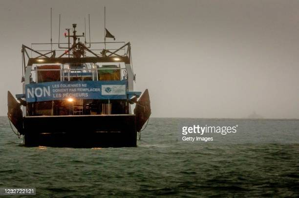 French fishing boat with a protest sign opposing new fishing licenses on May 6, 2021 in St Helier, Jersey. Up to 80 French fishing boats sailed to St...