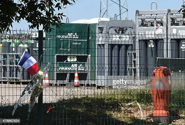 A French flag and flowers are placed on the fence of the Air Products gas factory where the head of the decapitated man was found in a suspected...