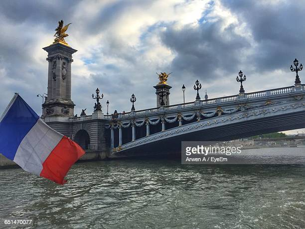 French Flag By Pont Alexandre Iii Over Seine River Against Cloudy Sky