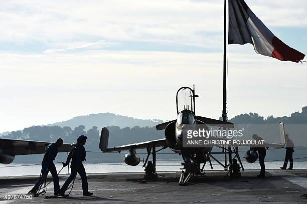 A French flag flies above French naval technicians working on the flight deck of the aircraft carrier CharlesdeGaulle at a military port in the...