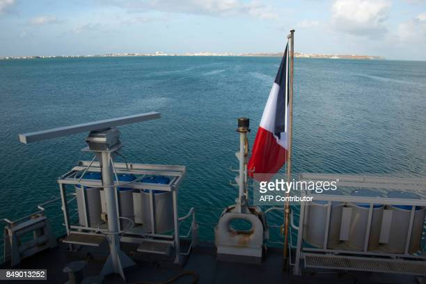 A French flag flies on the French marine frigate Germinal docked at the port of Galisbay on the French Caribbean island of Saint Martin to deliver...
