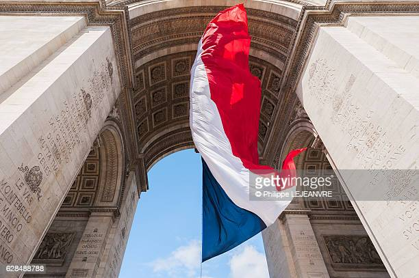 French flag floating under the Triumphal Arch in Paris, France