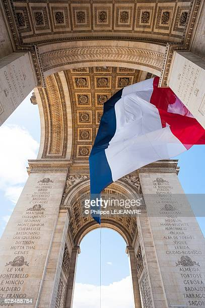 french flag floating under the triumphal arch in paris vertical - bastille day stock pictures, royalty-free photos & images