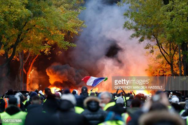 French flag floats as fire is burning during a protest of Yellow vests against rising oil prices and living costs on December 1 2018 in Paris...