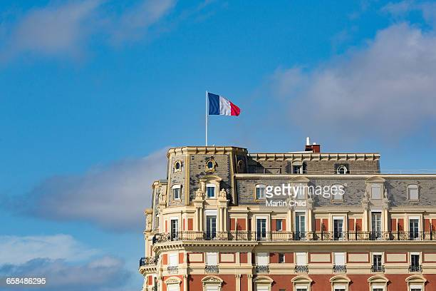 french flag flying over building in biarritz - biarritz stock pictures, royalty-free photos & images