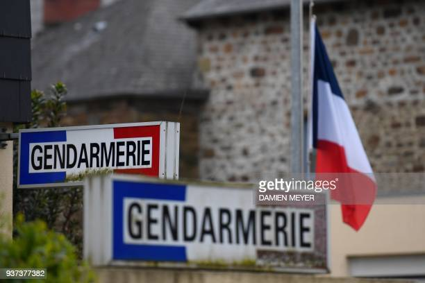 A French flag is seen lowered to half mast on March 24 2018 at the gendarmerie in HédéBazouges suburb of Rennes western France as a tribute to French...