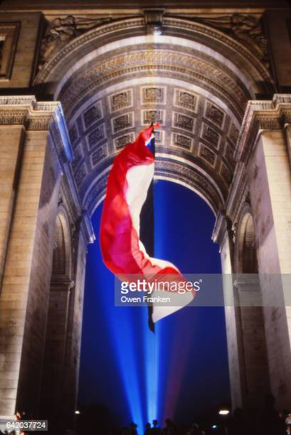 french flag waving at the arc de triomphe, paris, on bastillle day - bastille day stock pictures, royalty-free photos & images