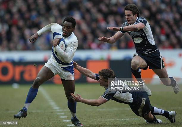 French flanker Fulgence Ouedrago tries to escape from Scottish wing Thom Evans and Scottish flyhalf Phil Godman during their six Nations rugby union...