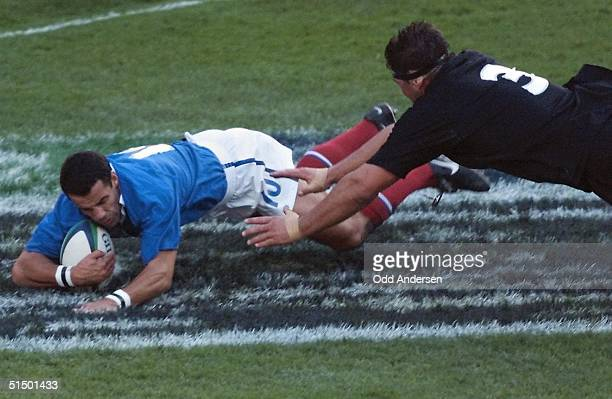 French flyhalf Christophe Lamaison scores a try as New Zealand prop Craig Dowd dives on him during the Rugby World Cup semifinal match between New...