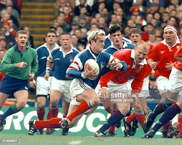French flyhalf Thomas Castaignede breaks away from the Welsh defense 05 april during the final match of the Five Nations tournament at Wembley in...