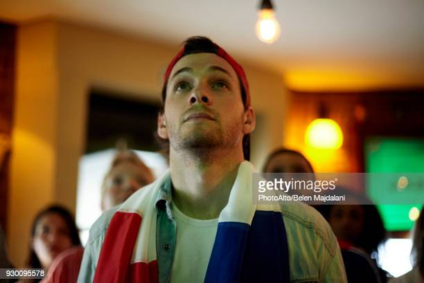 french football fan watching match in bar - fan enthusiast stock photos and pictures