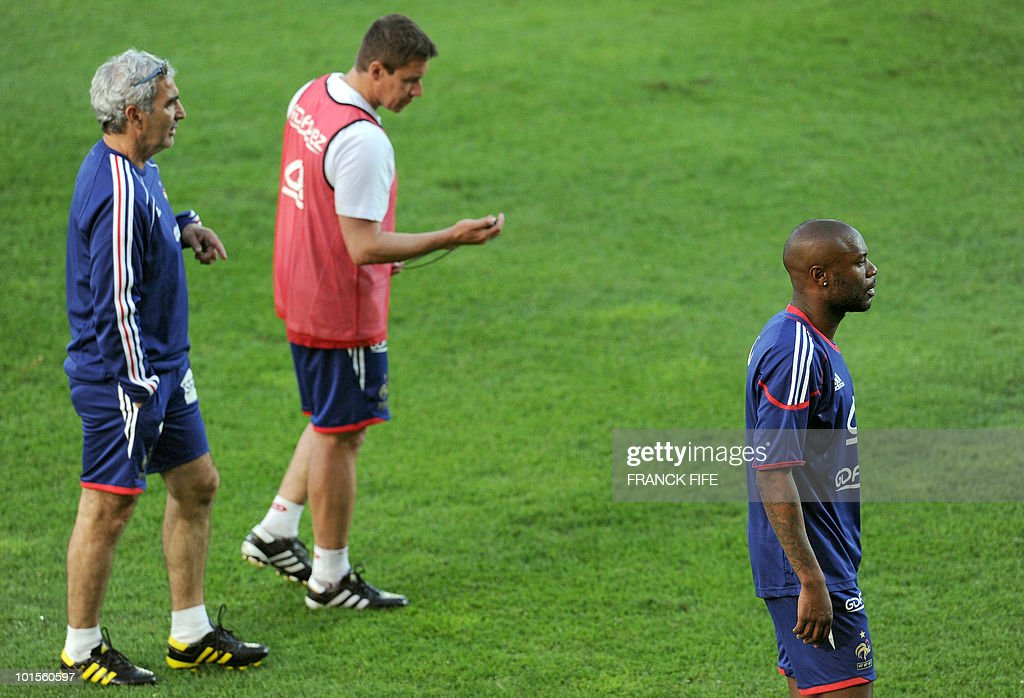 French football national team defender William Gallas (R) who complains of stomach pains, leaves the training session as physical assistant Robert Duverne (C) and coach Raymond Domenech (L) discuss, on June 2, 2010 at the Michel Volnay stadium in Saint-Pierre, on the French Indian Ocean island of La Reunion, as part of the preparation for the upcoming World Cup 2010. France have one remaining friendly scheduled against China in Reunion on June 4, 2010. They open their World Cup campaign against Uruguay on June 11.