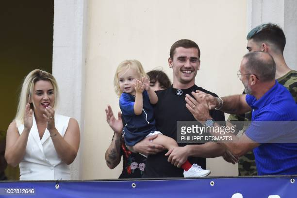 TOPSHOT French football player Antoine Griezmann holds his daughter Mia as he celebrates with his wife Erika and father Alain in his hometown of...