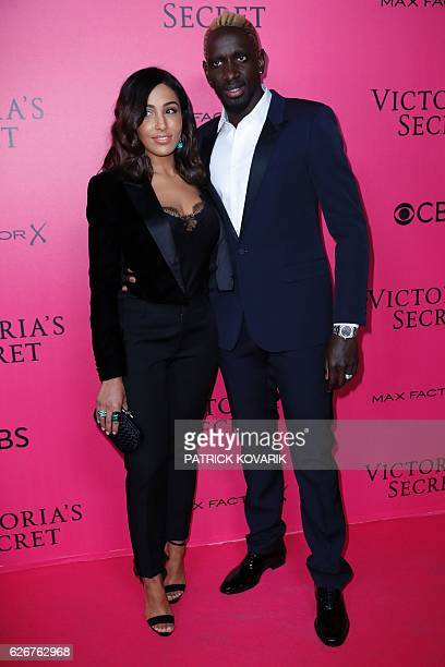 French football player Mamadou Sakho and his wife Majda Sakho pose on the pink carpet upon their arrival for the 2016 Victoria's Secret Fashion Show...