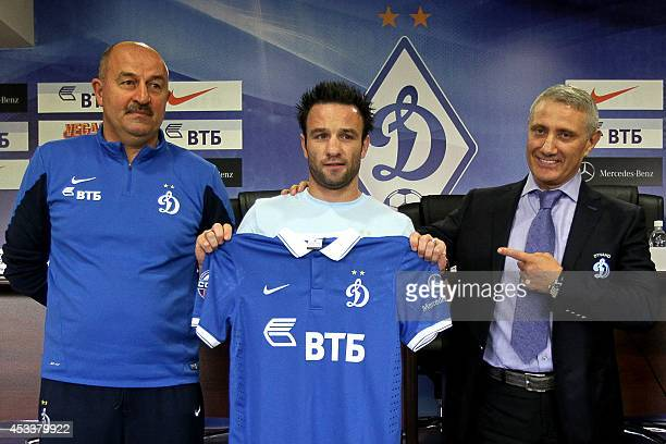 French football player Mathieu Valbuena poses while holding his new Russian football club Dynamo Moskva jersey next to Dynamo Moskva's head coach...