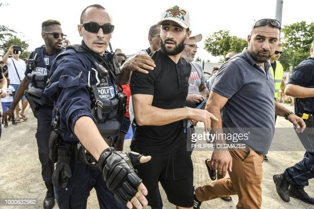 French football player Nabil Fekir is escorted by police as he arrives to celebrate in his home town of Vaulx-en-Velin near Lyon, southeastern France...