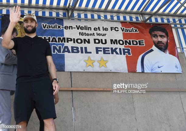 """French football player Nabil Fekir waves next to a poster reading """"World champion"""" in his home town of Vaulx-en-Velin near Lyon, southeastern France..."""