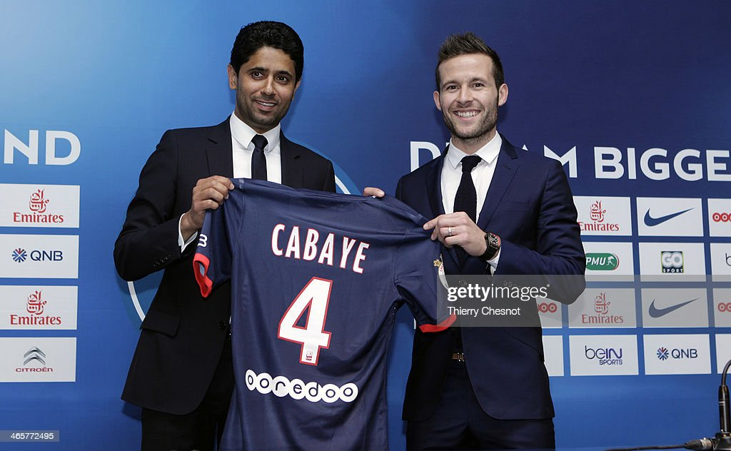 French football player Yohan Cabaye poses with PSG President Nasser al-Khelaifi and his new club shirt and during a press conference after completing a transfer from Newcastle United to Paris St Germain, at the Parc des Princes stadium on January 29, 2014 in Paris, France.