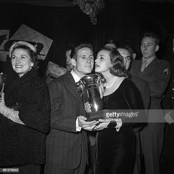 French footballer Raymond Kopa , flanked with his wife Christiane , poses on November 18, 1955 after French actress Jeanne Moreau gave him a cup for...