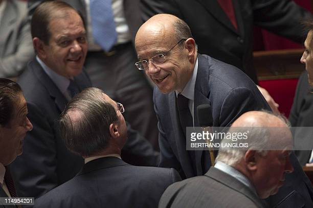 French Foreign Affairs minister Alain Juppe speaks to colleagues prior to the session of questions at the National Assembly on May 31 2011 in Paris...