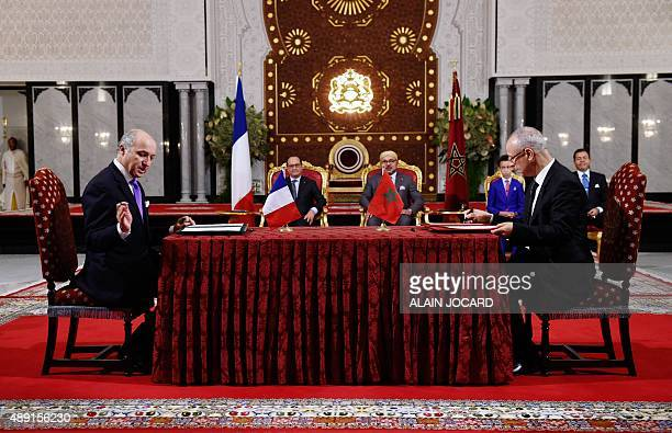 French Foreign Affairs minister Laurent Fabius and Moroccan minister of religious affairs Ahmed Toufik sign documents as part of a bilateral...