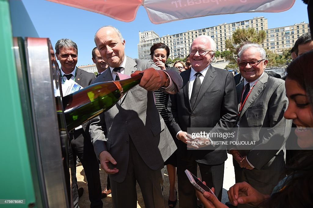 French Foreign Affairs minister Laurent Fabius recycles a bottle as and President of the Provence-Alpes-Cote d'Azur regional council Michel Vauzelle (2R) looks on at the 'village of the solutions' on June 05, 2015 during the MEDCOP21 climate summit at the Villa Mediterranee building in Marseille, southern France.