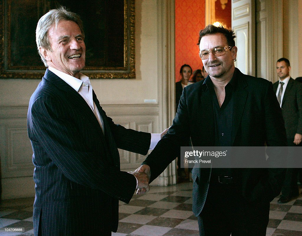 French Foreign Minister, Bernard Kouchner (L) shakes hands with lead singer Bono of Irish rock band U2 at Quai d'Orsay on September 17, 2010 in Paris, France.