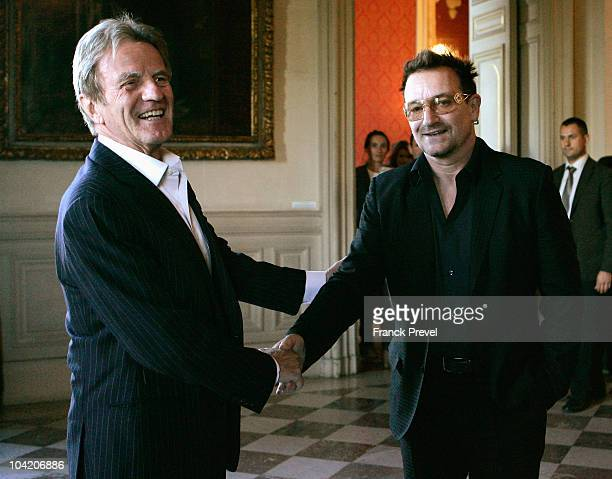 French Foreign Minister Bernard Kouchner shakes hands with lead singer Bono of Irish rock band U2 at Quai d'Orsay on September 17 2010 in Paris France