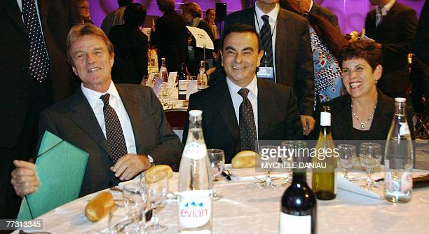 French Foreign Minister Bernard Kouchner smiles flanked by Renault and Nissan CEO Carlos Ghosn and Ghosn's wife Rita at a plenary luncheon on the...
