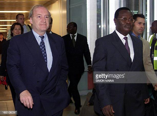French Foreign Minister Hubert Vedrine walks next to his Kenyan counterpart Chris Obure upon his arrival at the Jomo Kenyatta International Airport...