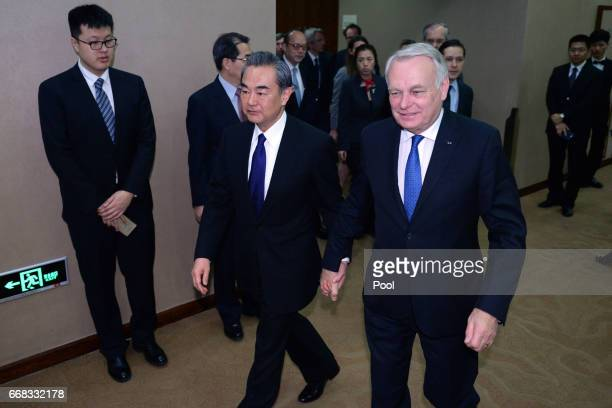 French Foreign Minister JeanMarc Ayrault right arrives with Chinese Foreign Minister Wang Yi for their meeting on April 14 2017 at the Ministry of...