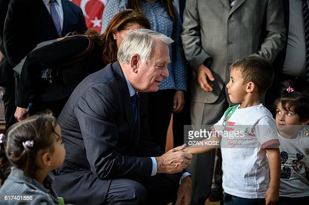 French Foreign Minister JeanMarc Ayrault shakes hands with a child during a visit to a refugee camp in the Kilis district of Gaziantep southeastern...